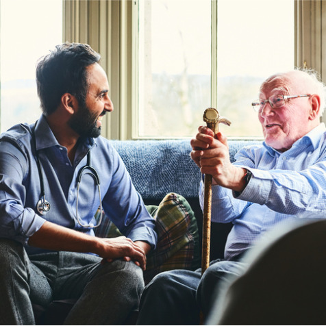 Picture of older man being visited by doctor at home