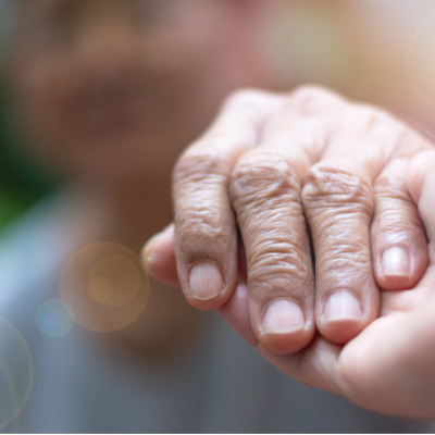 caregiver holding hands with older person