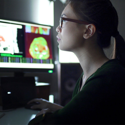 Researcher looking at computer screens with physiology images on them
