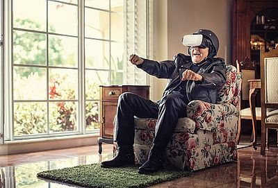 Elderly man smiling and sitting in a chair with a virtual reality headset on