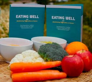Book cover in front of several examples of healthy foods including, carrots, cauliflower, broccoli, apples