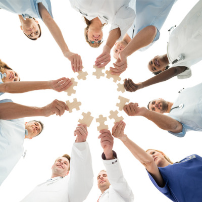 Medical team holding jigsaw puzzle pieces together
