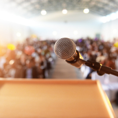 Low-angle photo of a microphone on a podium looking out over a blurred image of the audience